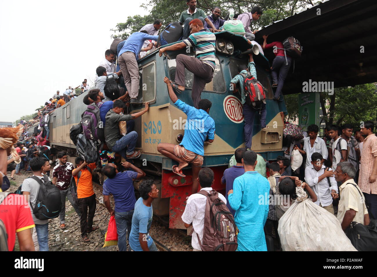 Risky journey not able to return home. Day after tomorrow Muslim religion biggest festival will begin. So lots of people starting to return home. Bus and air price is too high for low income people. Low income people traveled by train roof. The train already started and full. The guy fall from running train and lost his hand and leg Credit: RONY BARUA/Alamy Live News - Stock Image