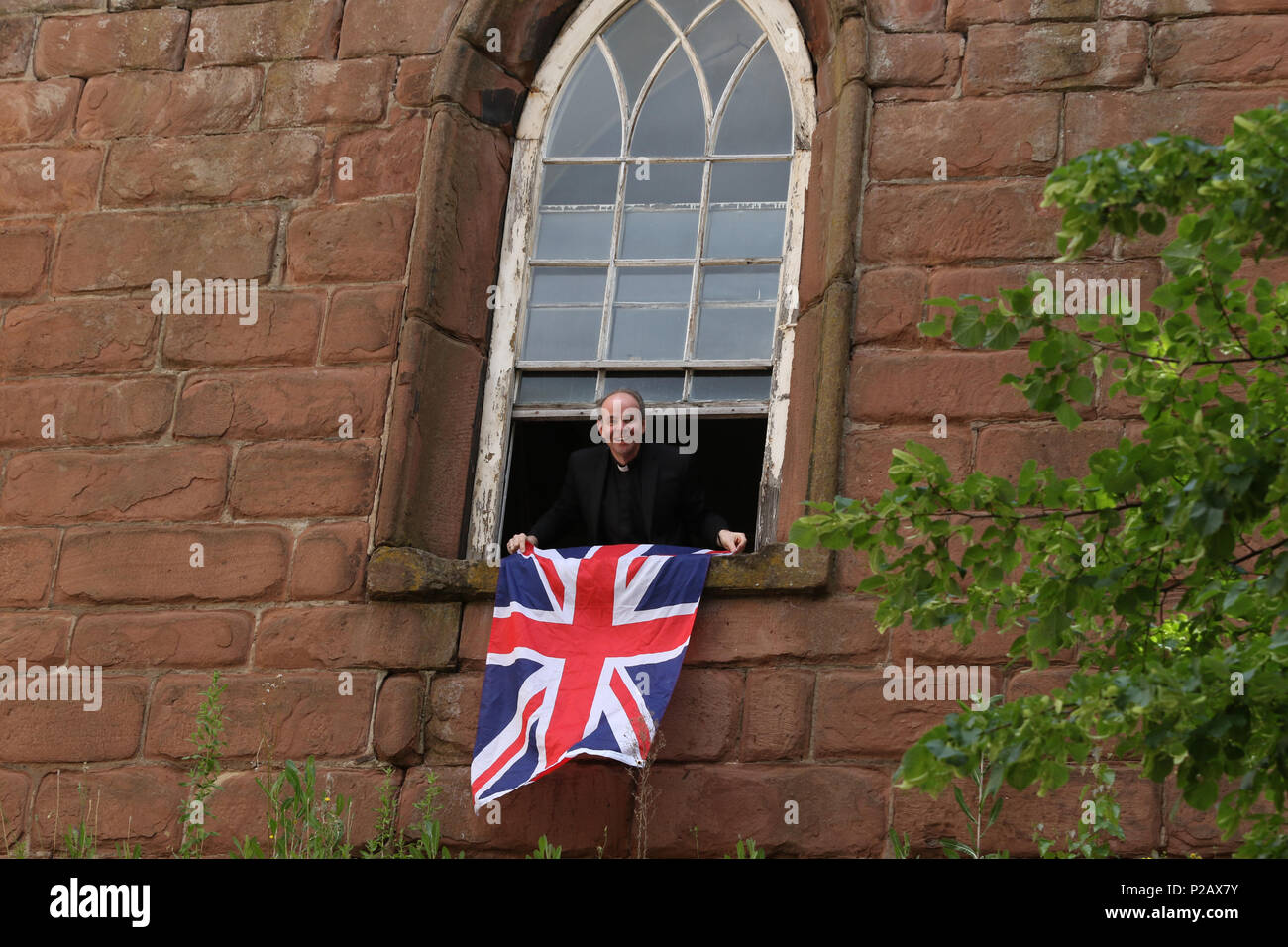 A member of the clergy hangs out a Union Jack Flag before HM Queen Elizabeth II and Meghan Markle, Duchess of Sussex, visit Chester on their first public engagement together. Chester, Cheshire, on June 14, 2018. Credit: Paul Marriott/Alamy Live News Stock Photo