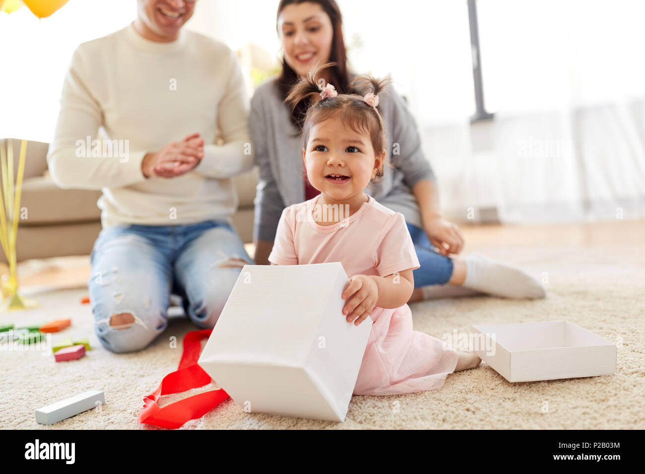 baby girl with birthday gift and parents at home - Stock Image