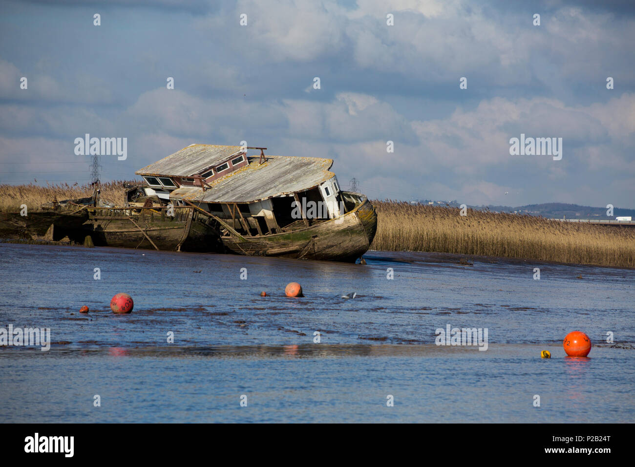A derelict houseboat and a couple of barges rotting on the mudflats of the River Exe at Topsham, Devon, England, UK - Stock Image
