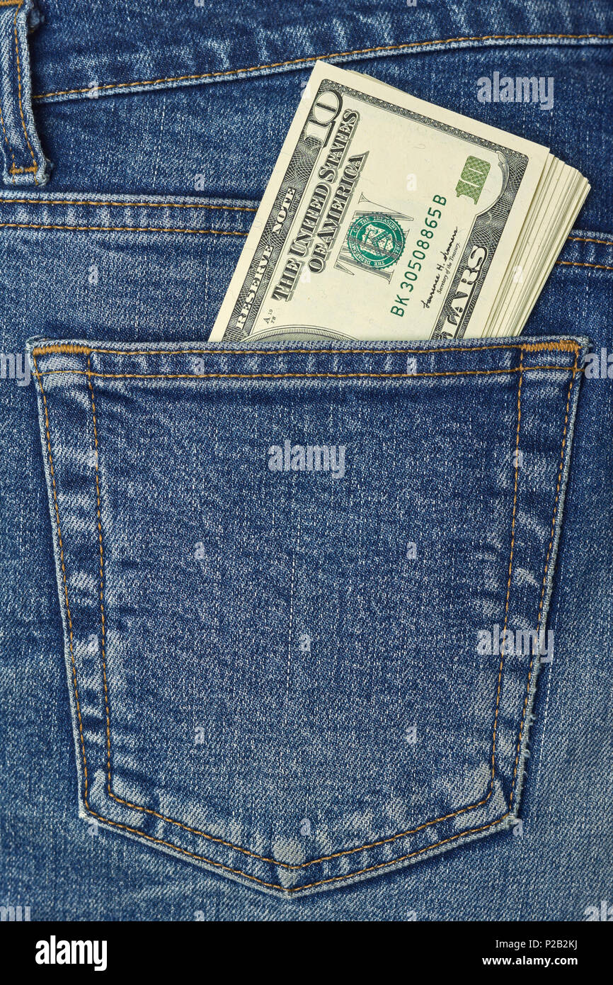 Pocket money. New dollar roll in hip pocket of worn blue jeans close-up - Stock Image