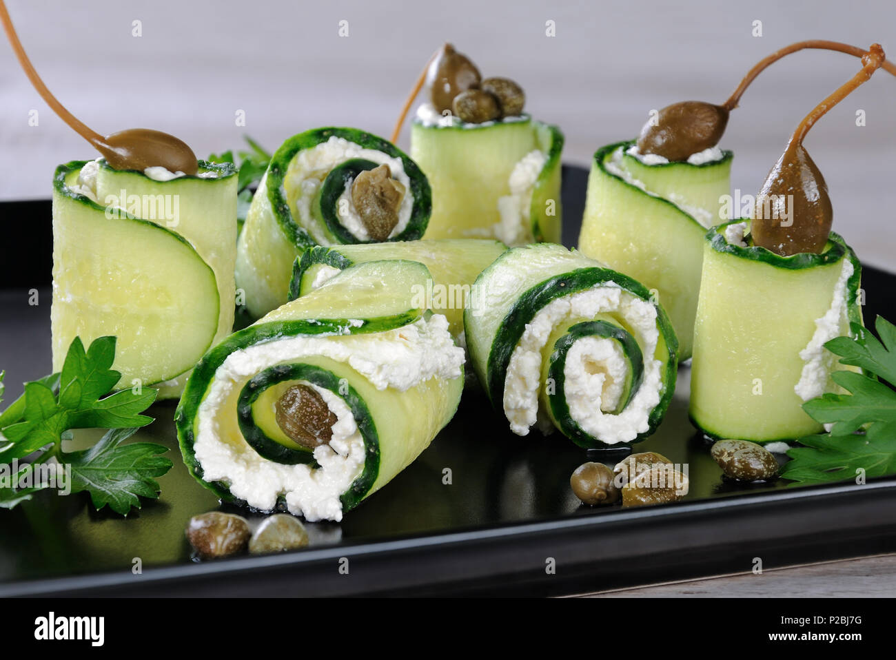 Cucumber rolls with ricotta filling and capers.   These rolls with the size of a bite -is a great option with a low fat content, which serves as a sna - Stock Image