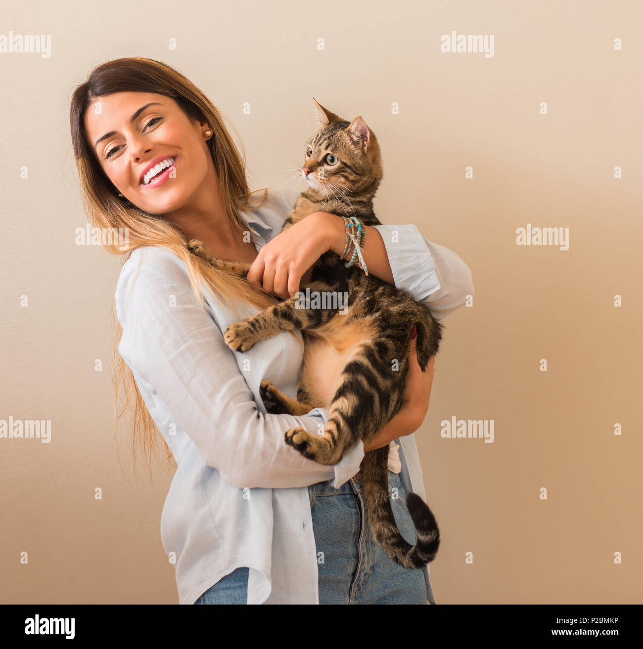 Young beautiful woman smiling cuddling cat with love at home. - Stock Image