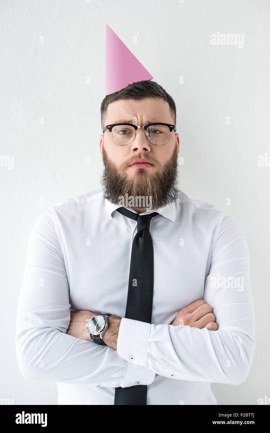 portrait of bearded businessman in formal wear and with party cone on head isolated on grey - Stock Image