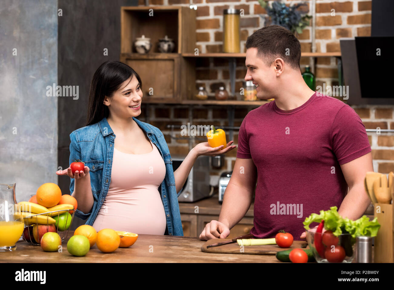 happy young pregnant couple smiling each other while cooking together at kitchen - Stock Image