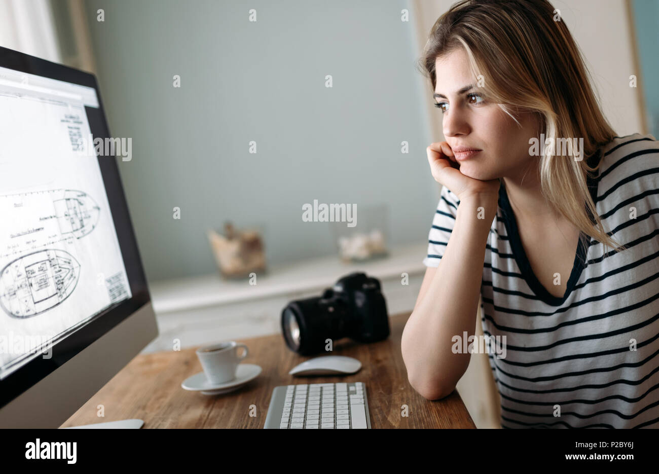 Young designer working on project at home - Stock Image