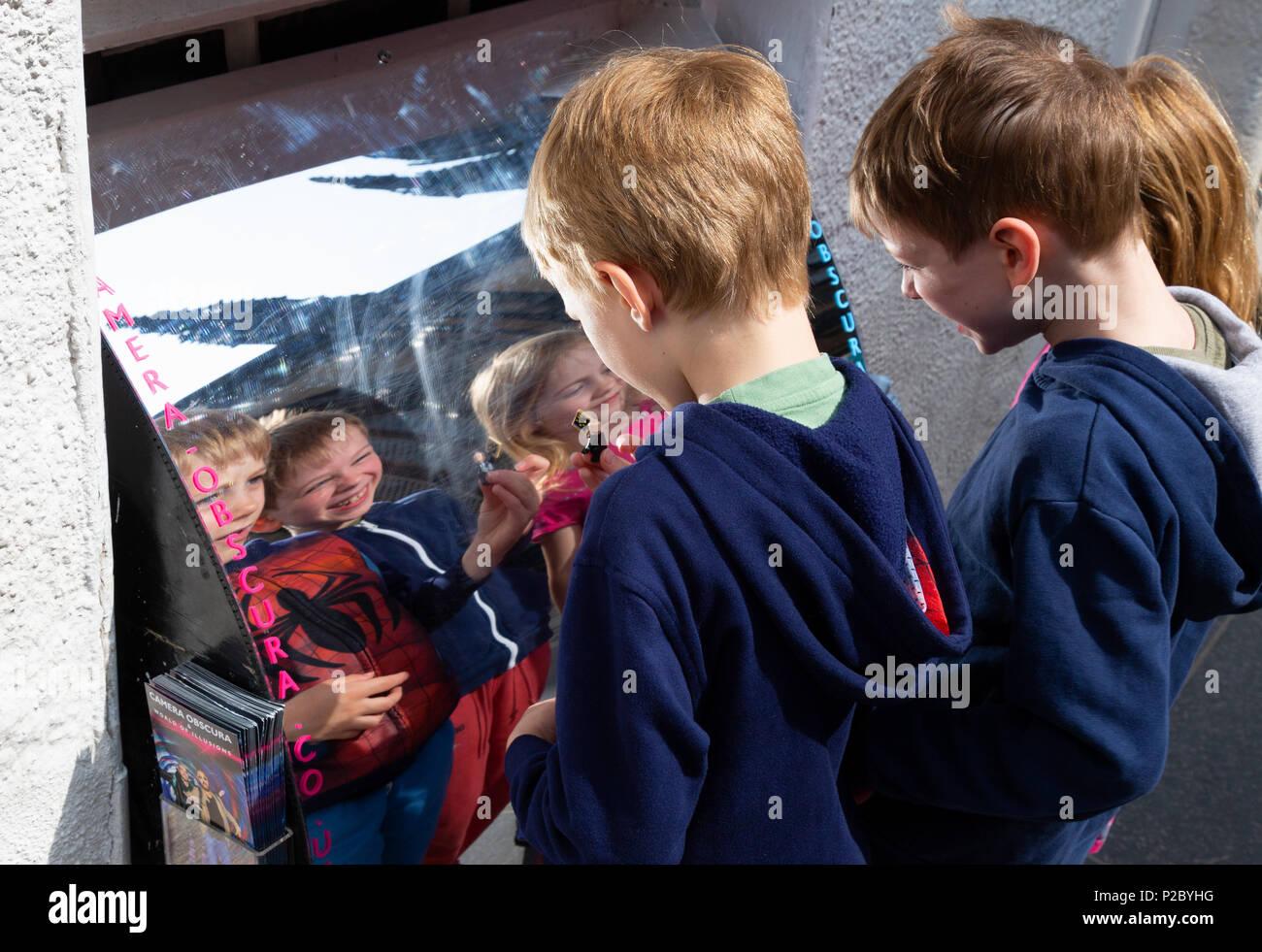 Happy children having fun with their reflection in a distortion mirror, Edinburgh. Scotland UK - Stock Image