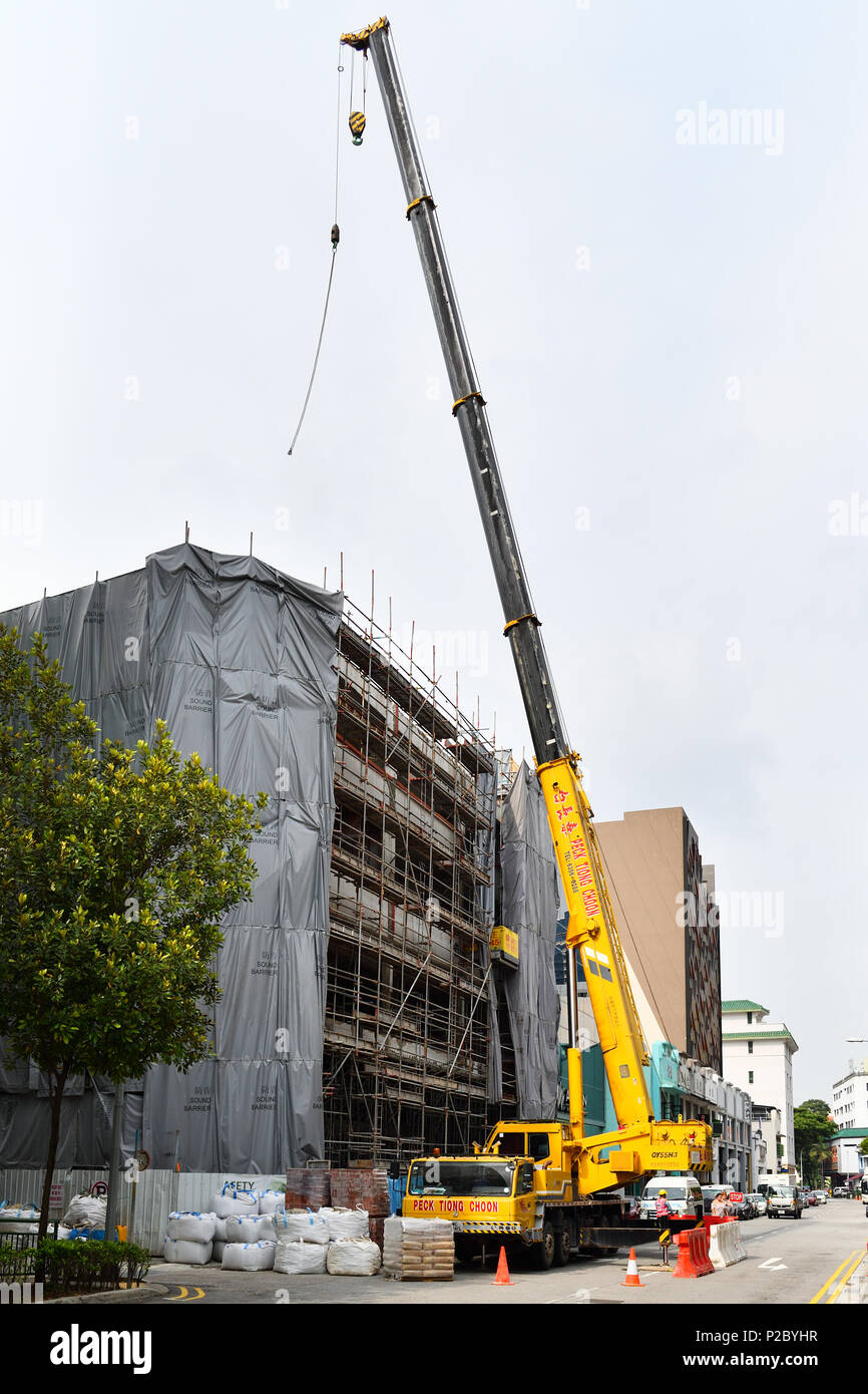 Singapore. Foreign workers operate a large telescopic crane used for construction. This is under the ownership of Peck Thiong Choon. - Stock Image