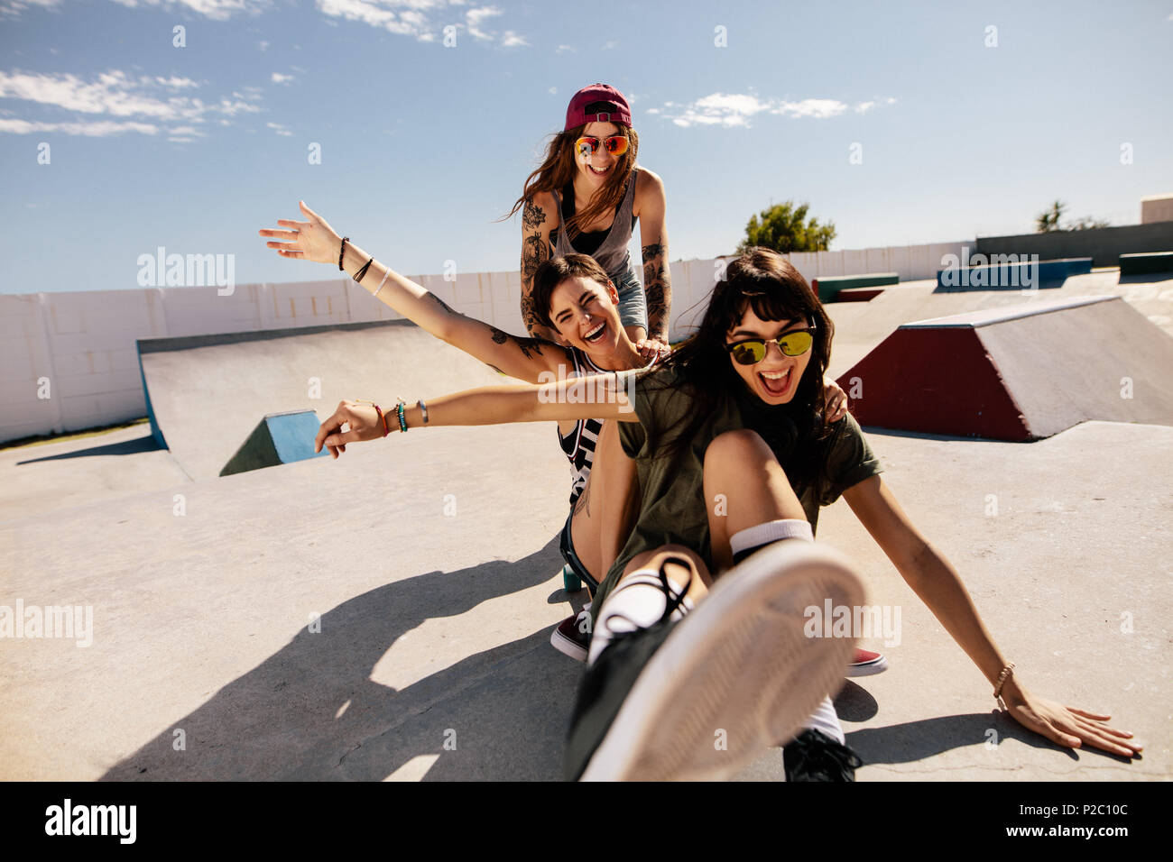 Three female friends playing with skateboard at the skate park. One woman pushing her friends from behind having fun and laughing. - Stock Image