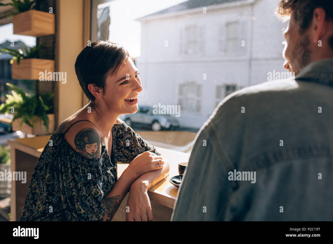 Young woman sitting at cafe with her boyfriend and smiling. Couple meeting at coffee shop and talking. - Stock Image