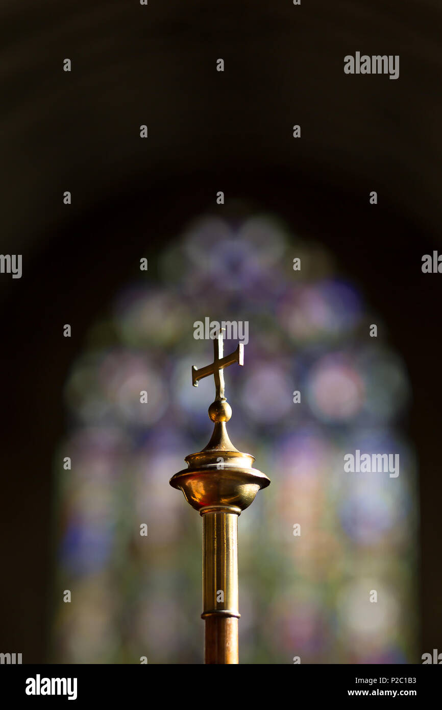 Arty, portrait close-up shot of brass cross with soft-focus stained glass window in background. Church interior of Christian faith, traditional C of E. - Stock Image