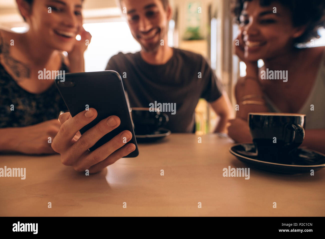 Three young people looking at mobile phone and smiling while sitting at restaurant table. Man showing something interesting to female friends during m - Stock Image