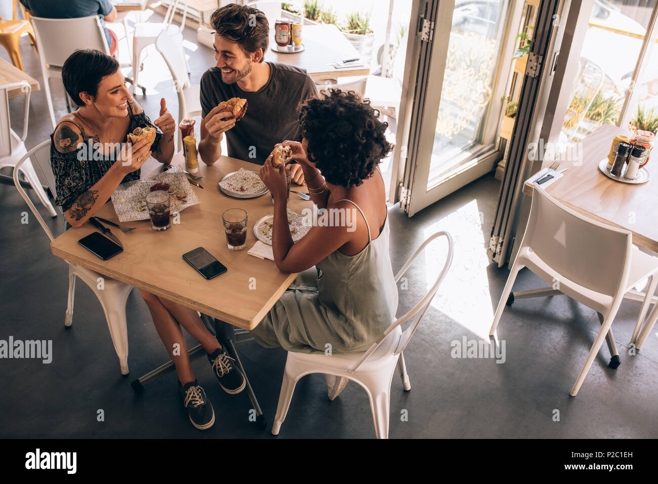 High angle view of three young friends having burger at a restaurant. Small group of man and women sitting around cafe table talking and eating. - Stock Image