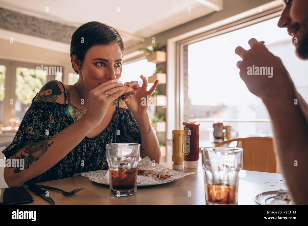Young woman eating burger with her boyfriend sitting around the table at a restaurant. Couple having burger at cafe. - Stock Image