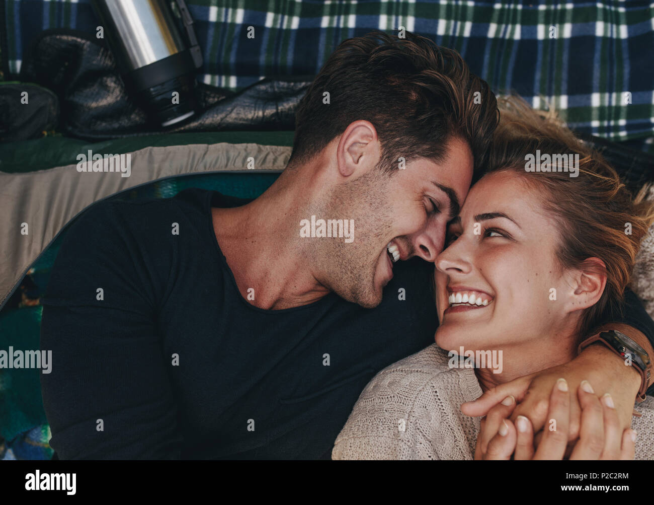Top view for romantic couple inside a tent. Smiling man and woman lying together and looking at each other in a tent. - Stock Image
