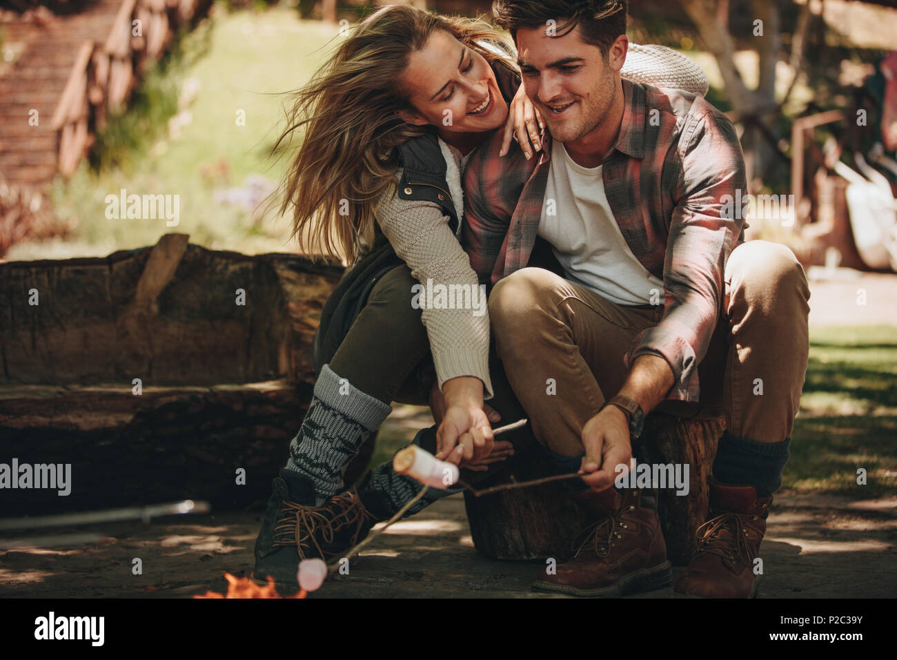 Happy man and woman sitting by fire and roasting marshmallows on sticks at campsite. Romantic couple having a great time on their camping. - Stock Image