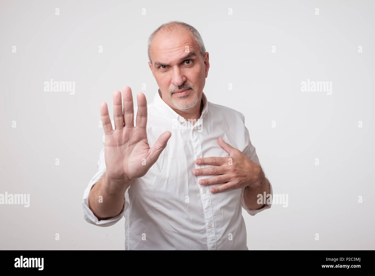 Mature man in yellow shirt showing sign stop with hand. - Stock Image