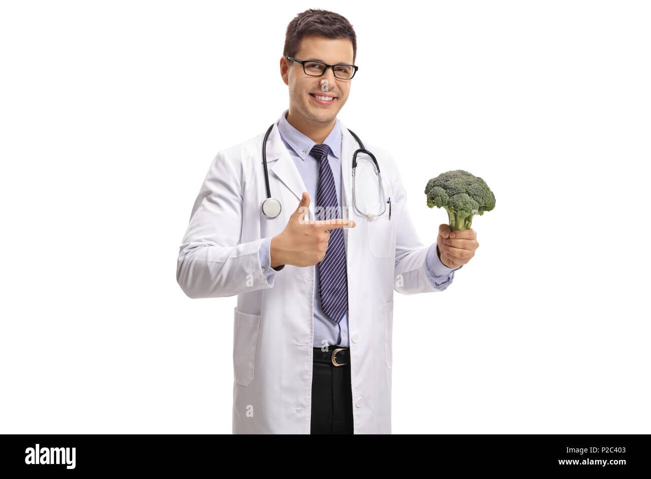 Doctor with broccoli pointing isolated on white background - Stock Image