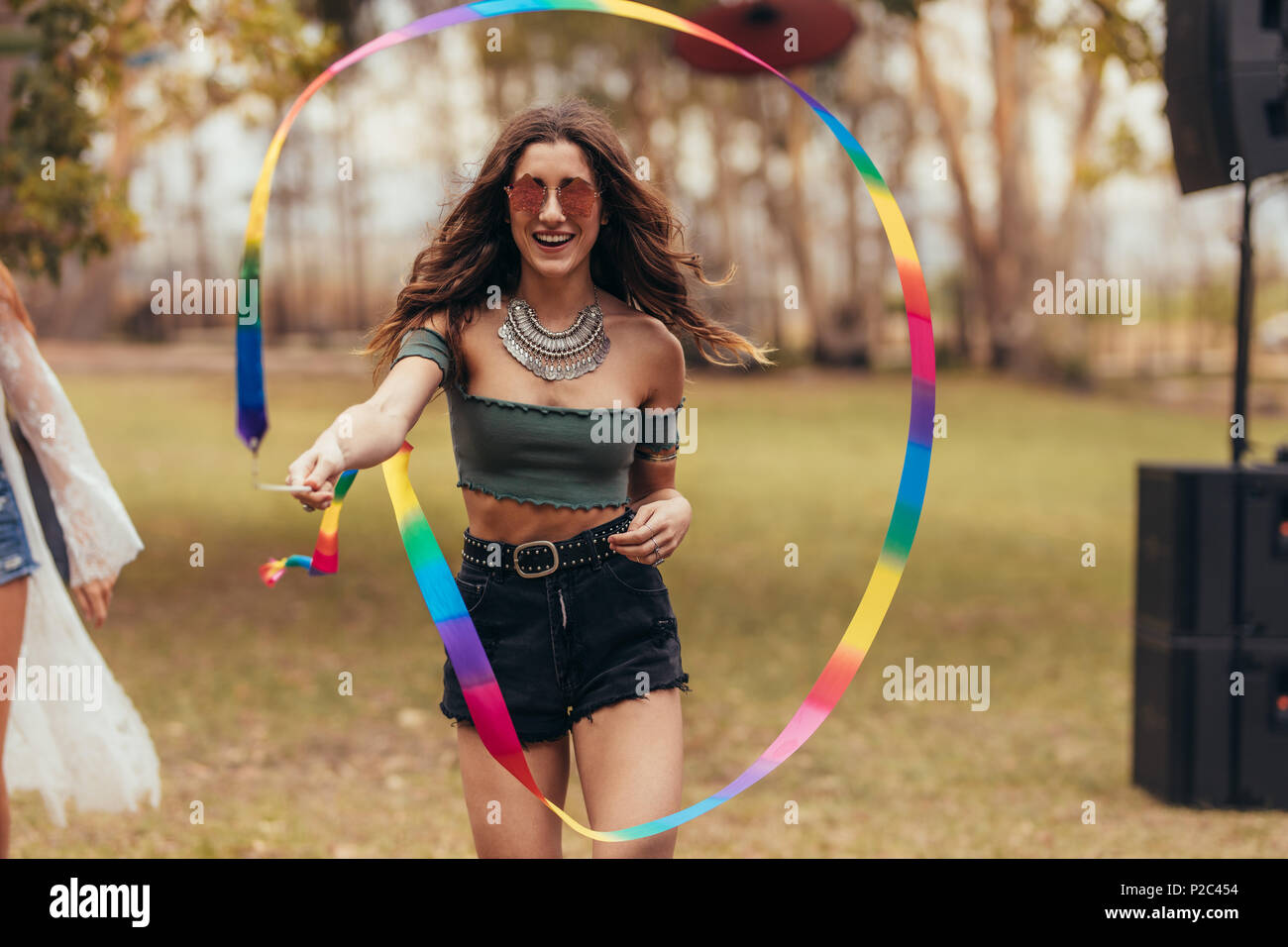 Beautiful young woman playing with ribbon stick at music festival. Female hipster enjoying at music festival. - Stock Image