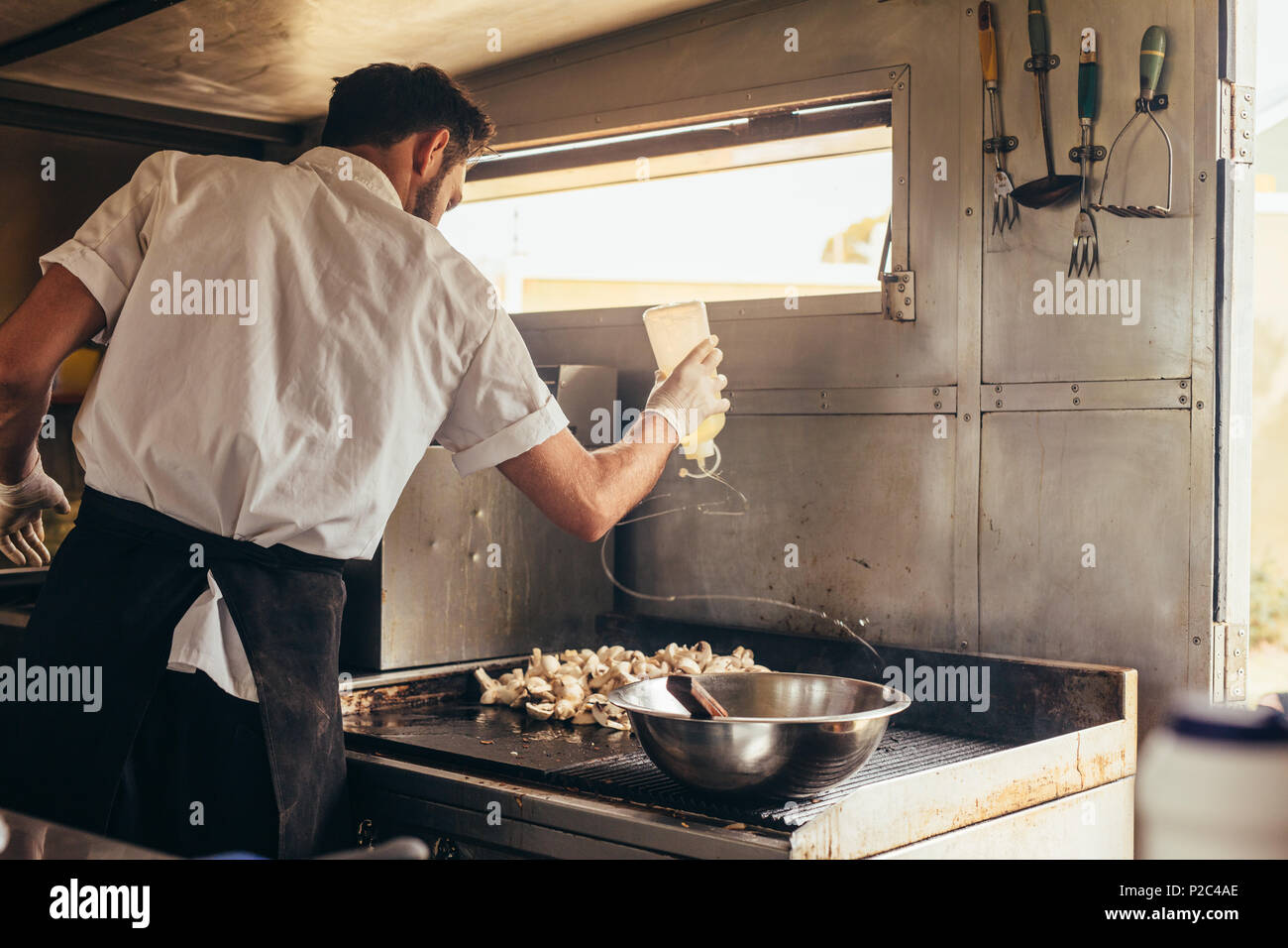 Young chef cooking some of his favorite dishes in a food truck. Man preparing food on stove in his food truck. - Stock Image