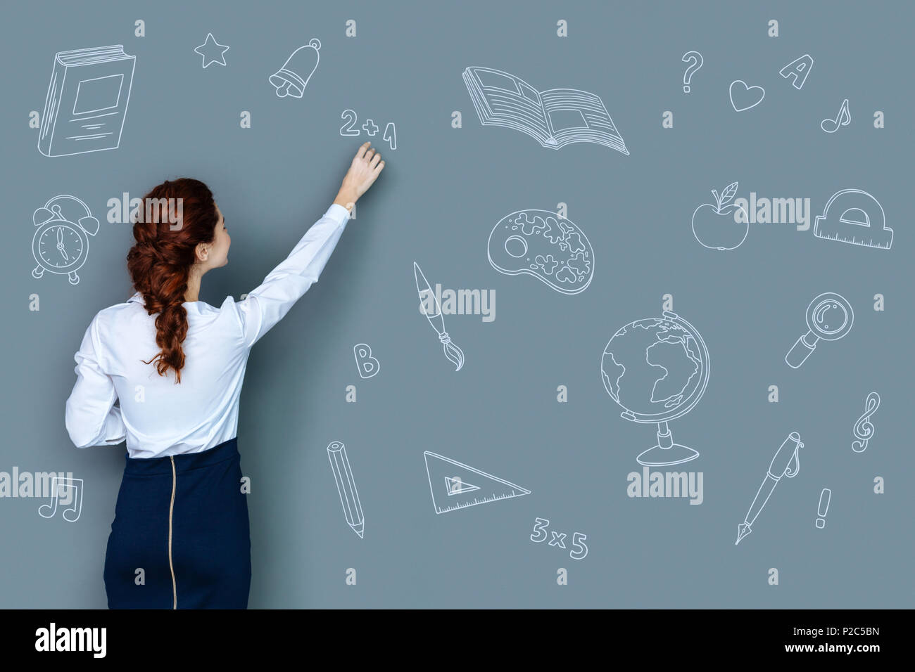 Clever teacher explaining a new topic and writing on the blackboard - Stock Image