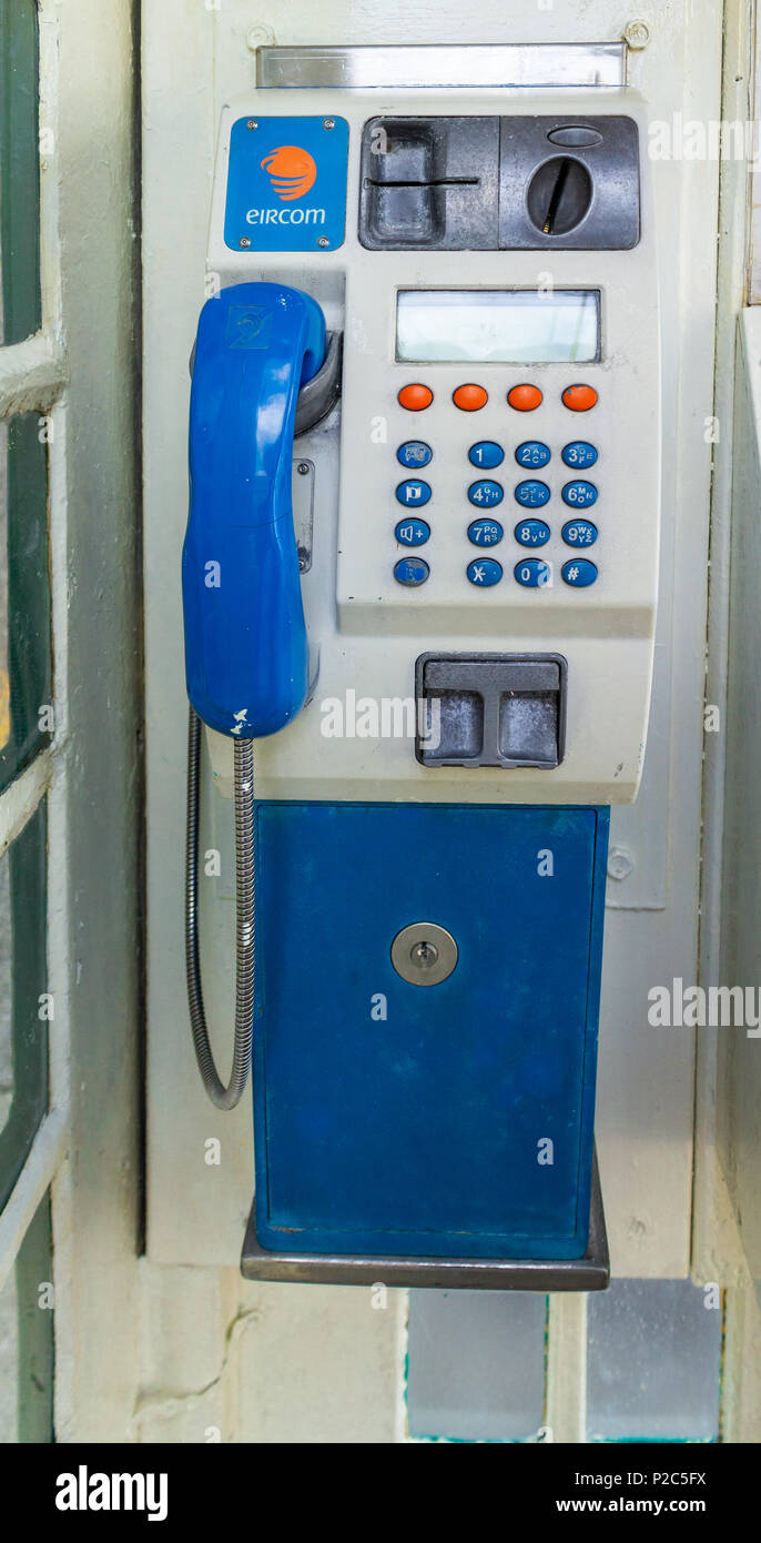 telephone kiosk or phone box in ireland with a coin operated telephone. - Stock Image