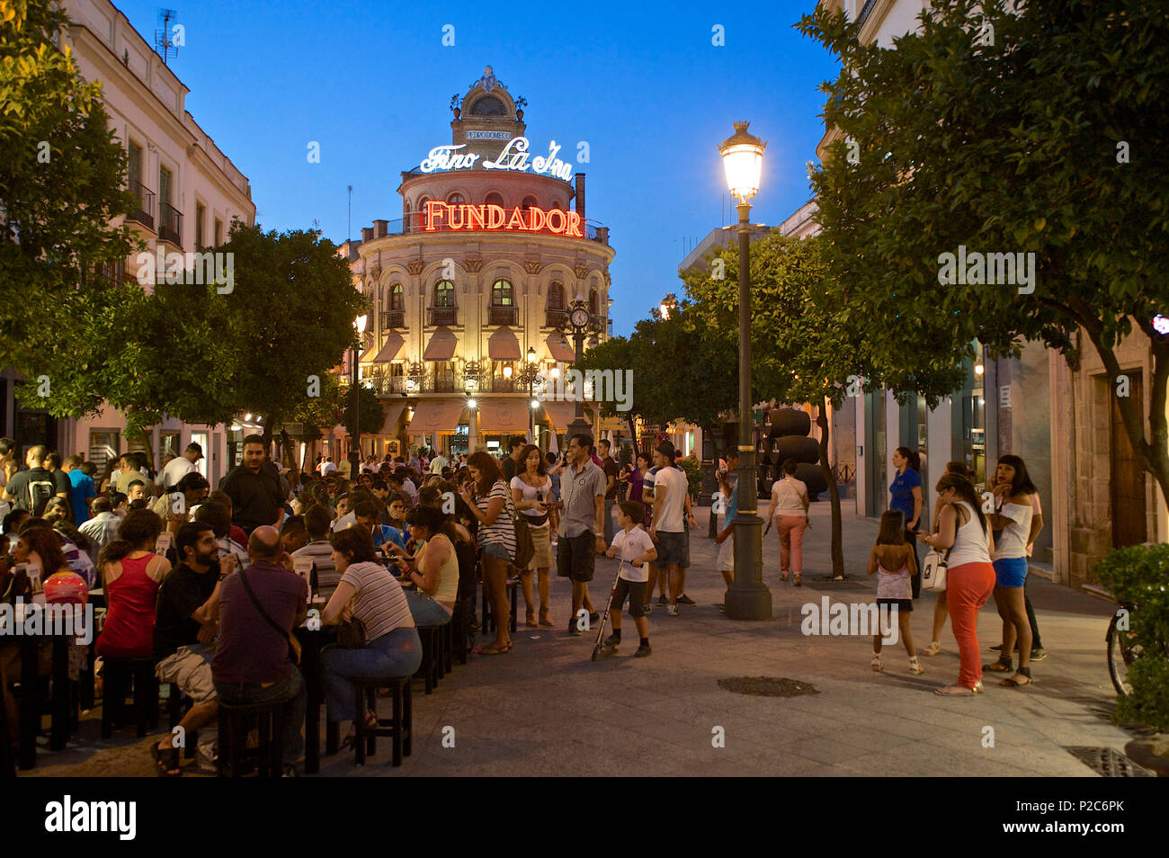 People at tables and in the street in the evening in the Calle Larga, Jerez de la Frontera, Andalusia, Spain, Europe Stock Photo