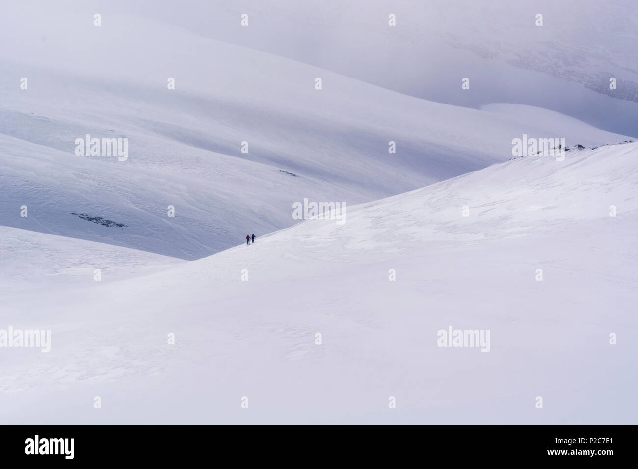 Two backcountry skiers ascending in the midst of large snow slopes, Simplon Region, Lepontine Alps, canton of Valais, Switzerlan Stock Photo
