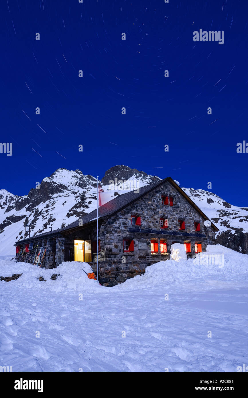 Full-moon over the Grialetsch hut 2542 m with Piz Radoent 3065 m and a carousel of stars above it, Grisons, Switzerland, Europe - Stock Image