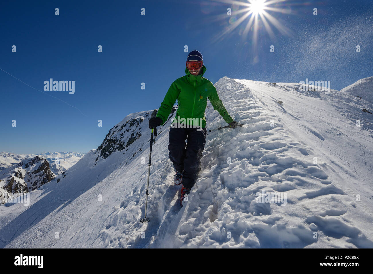 A mountaineer descending over the northern ridge of Piz Sarsura 3178 m, Grisons, Switzerland, Europe - Stock Image