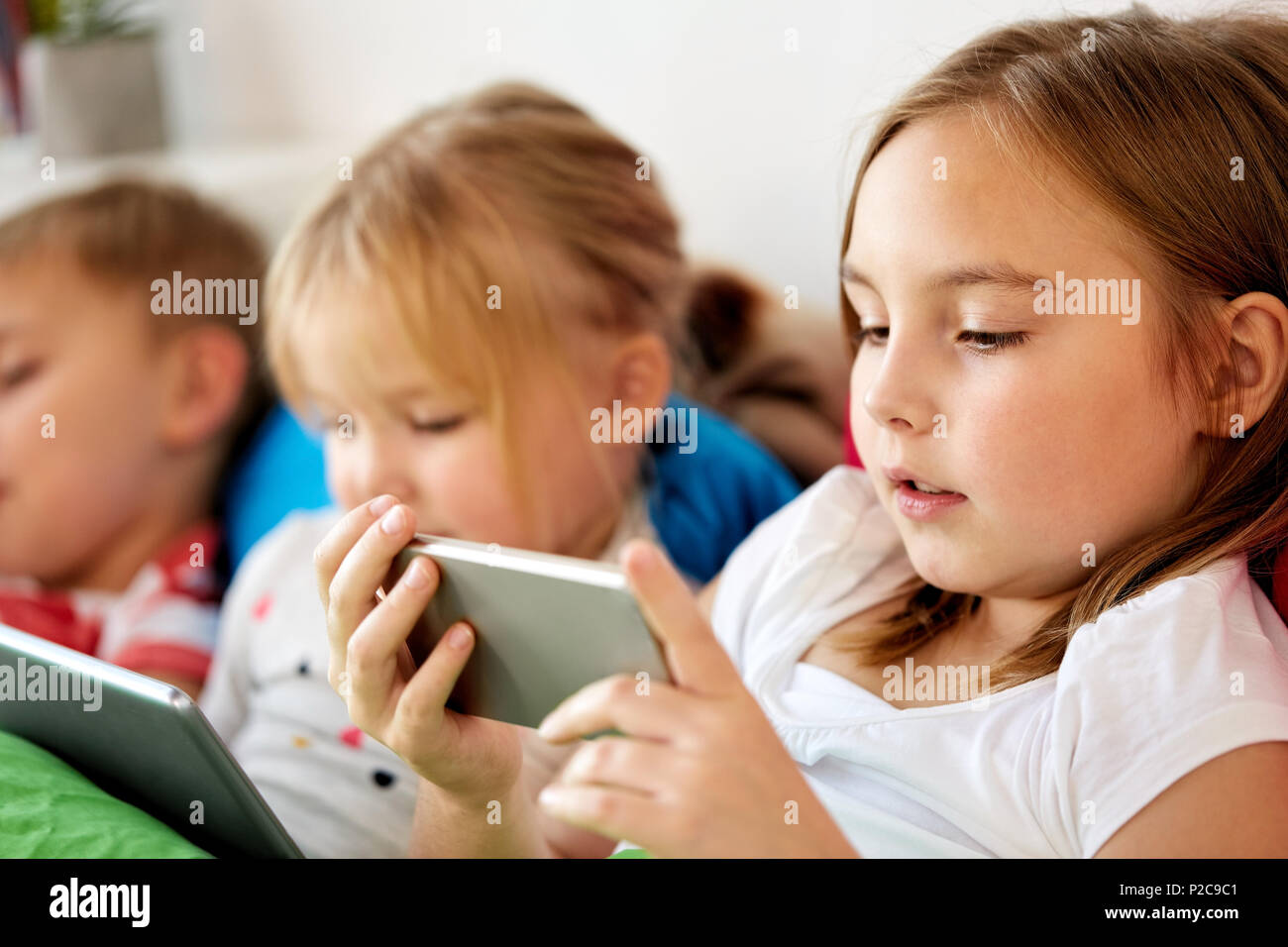 little kids with smartphone in bed at home - Stock Image
