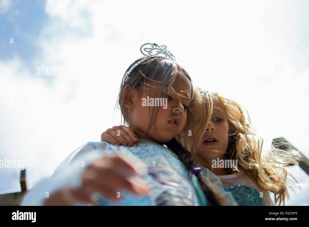 Young Asian girl wearing a princess dress and a tiara celebrating her birthday with her best friend hugging her tight - Stock Image