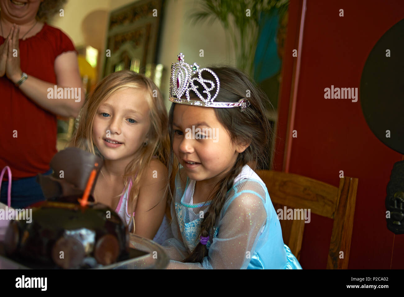 Cute little preteen Asian girl wearing a princess dress and a tiara blowing out the candles on her birthday cake with her best friend sitting with her - Stock Image