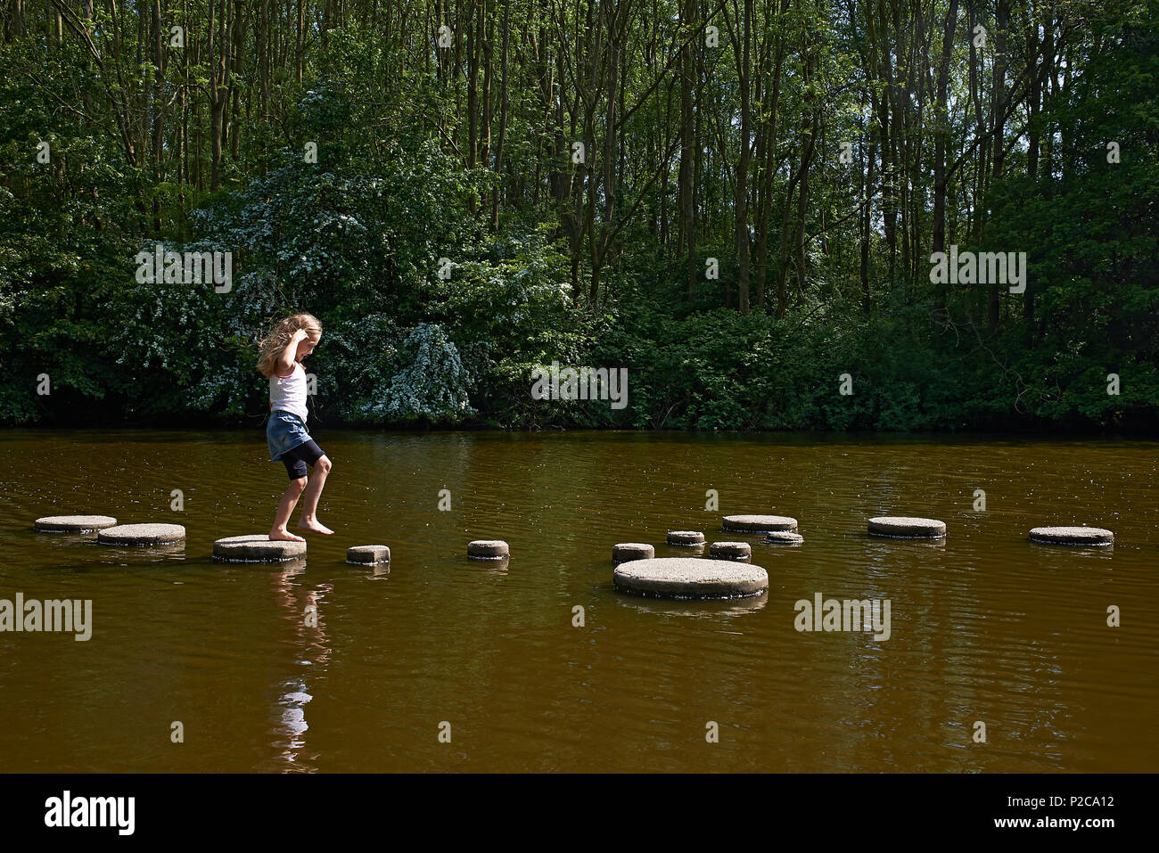 Young preteen girl walking across a stone path in the middle of a river trying out this challenge to find her path across without falling in the water Stock Photo