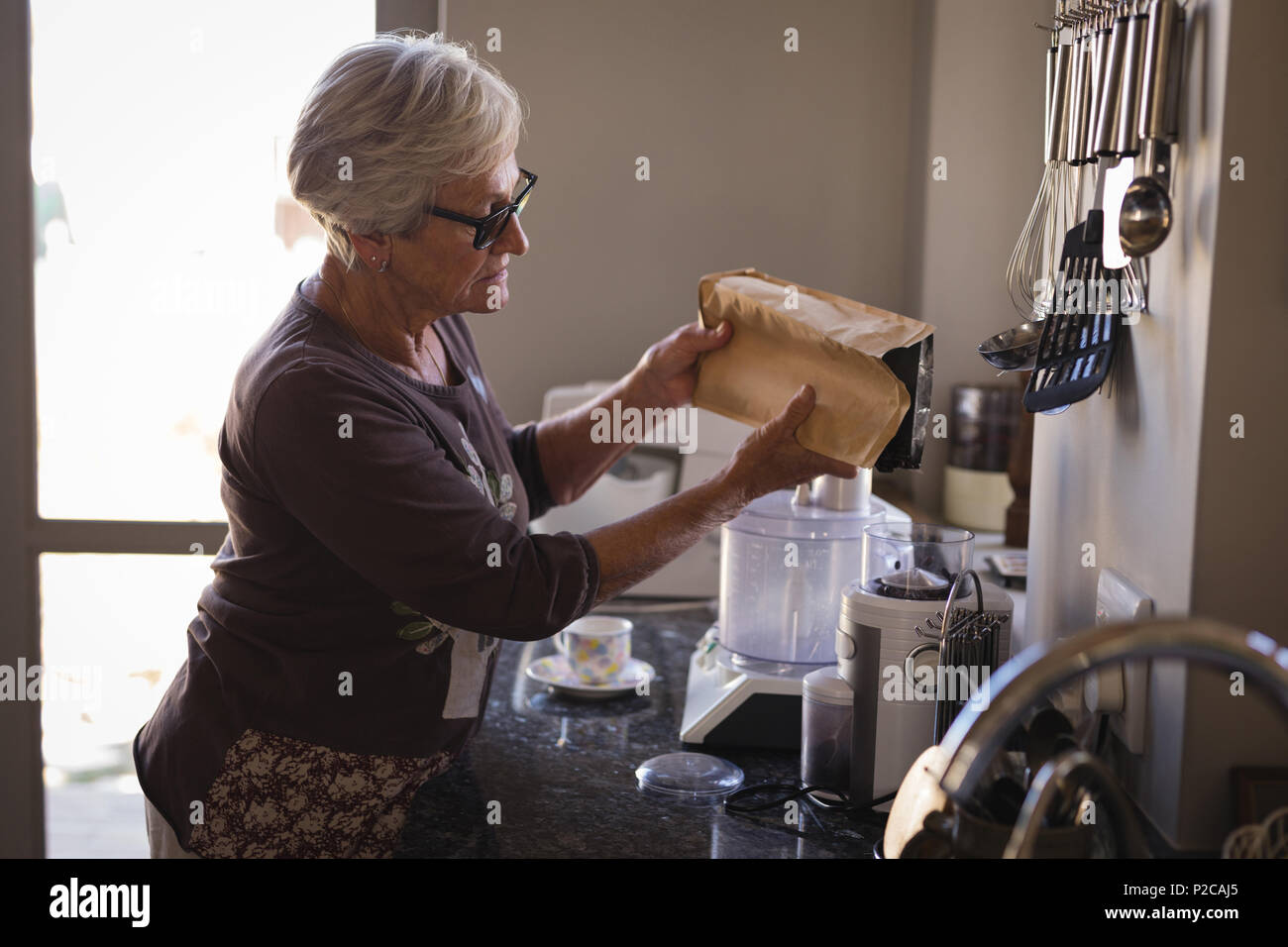 Senior woman putting milk in coffee maker - Stock Image