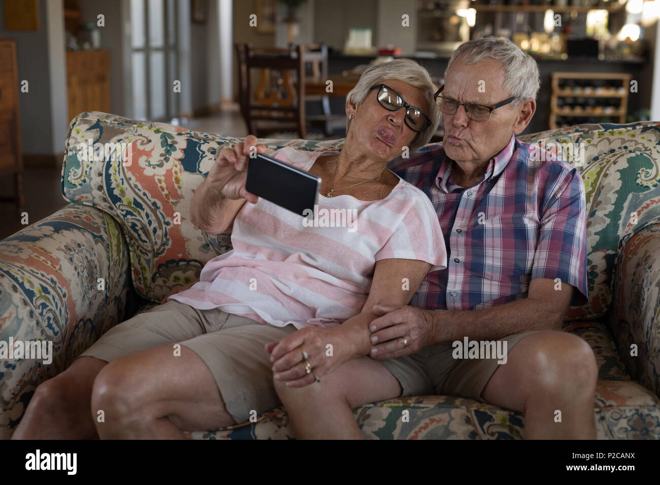 Senior couple taking selfie with mobile phone in living room Stock Photo