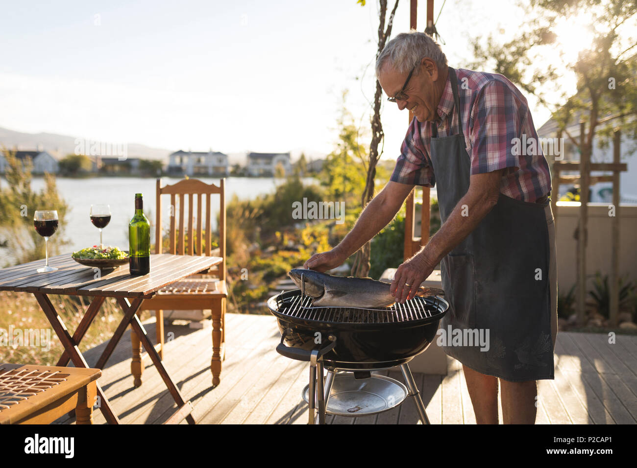Senior man cooking fish on barbeque - Stock Image