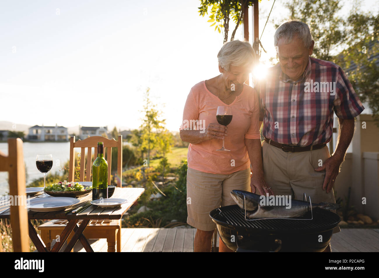 Senior couple cooking fish on barbeque - Stock Image