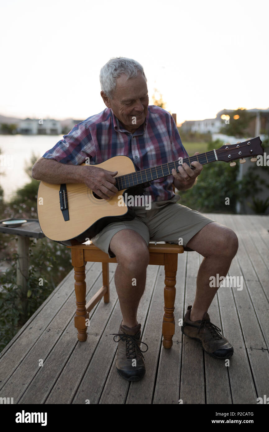 Senor man playing guitar in the porch - Stock Image