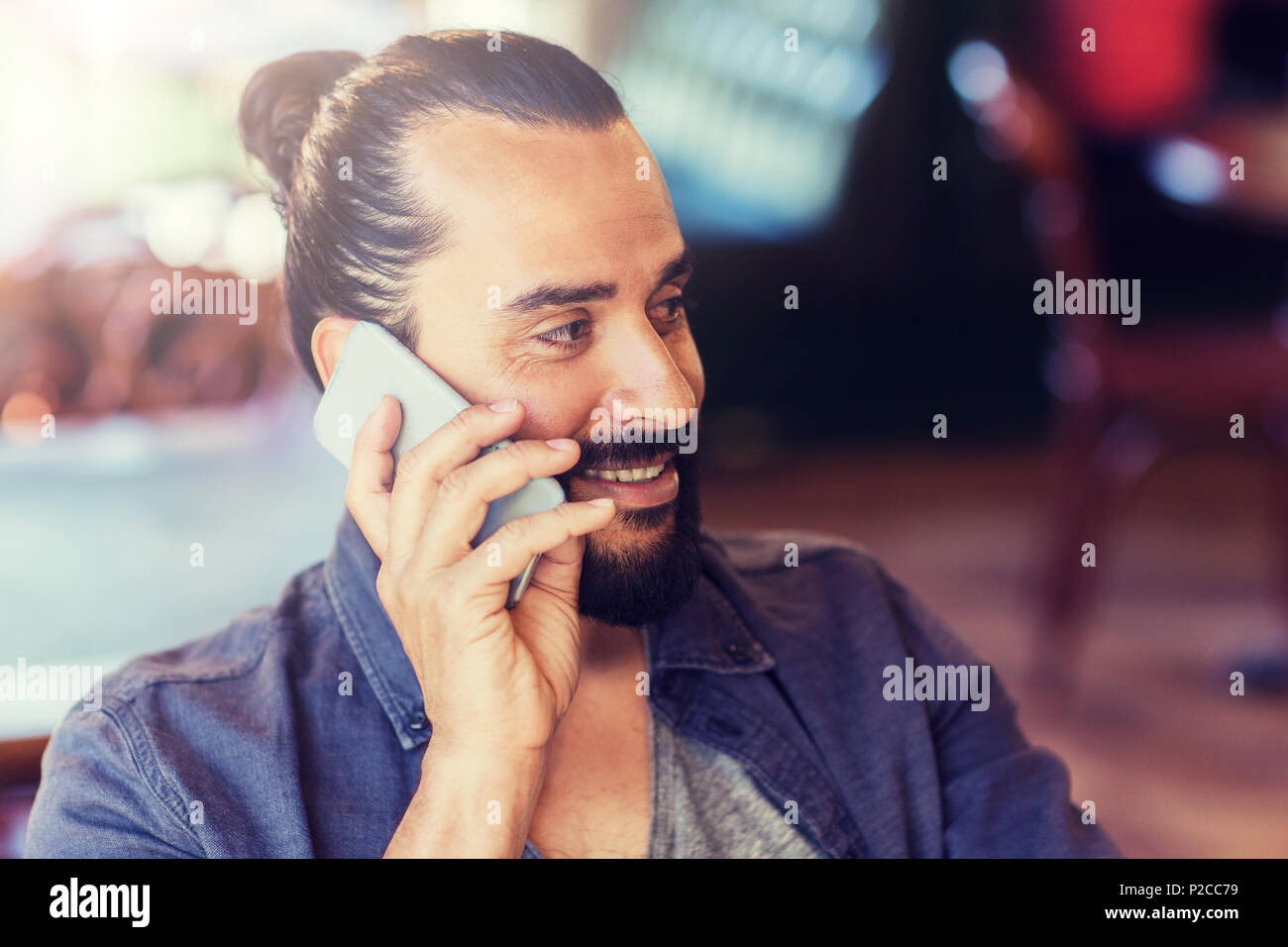 happy man calling on smartphone at bar or pub - Stock Image
