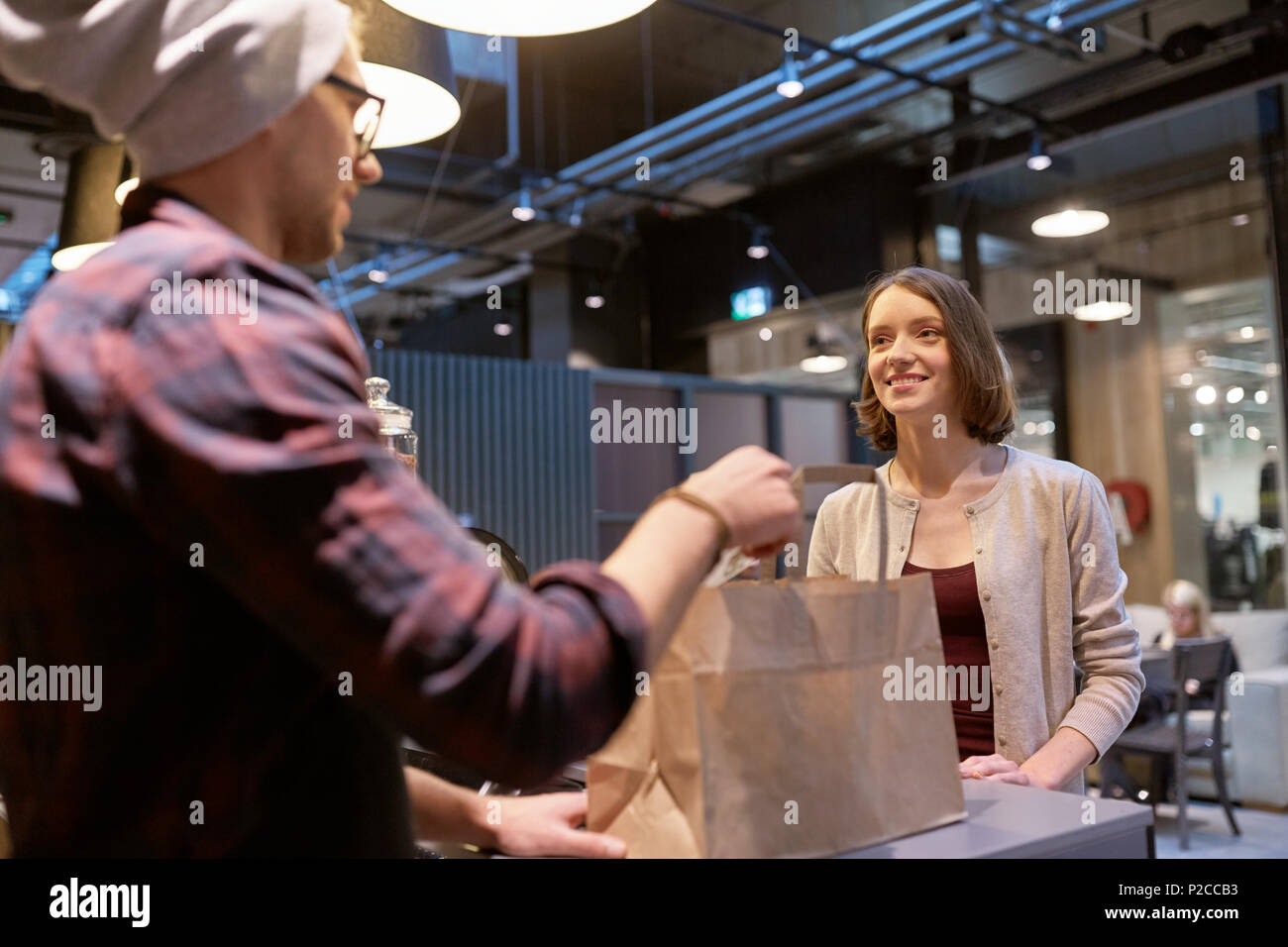 seller giving paper bag and money to woman at cafe - Stock Image