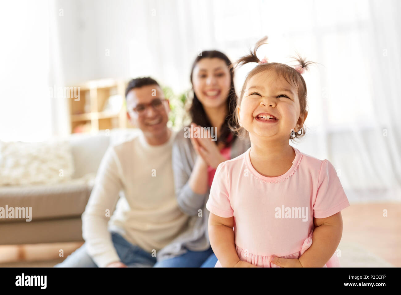 happy baby girl and parents at home - Stock Image