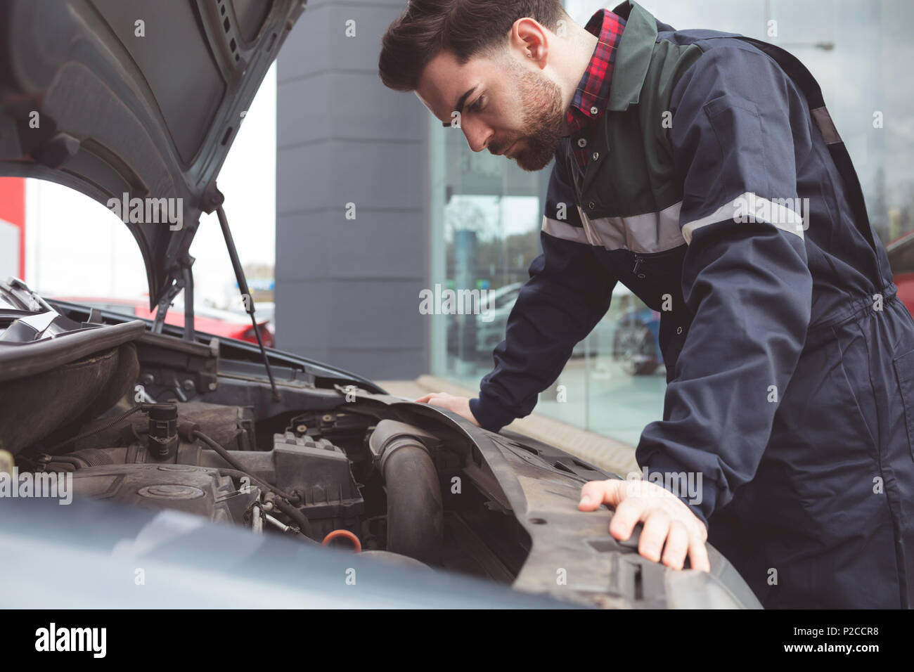 Male mechanic servicing car - Stock Image