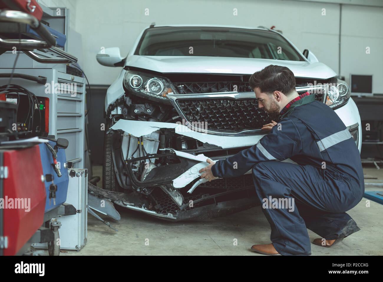 Mechanic examining damaged car - Stock Image