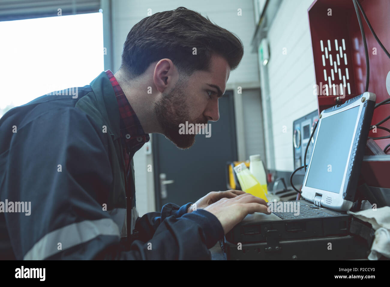 Attentive mechanic using laptop - Stock Image