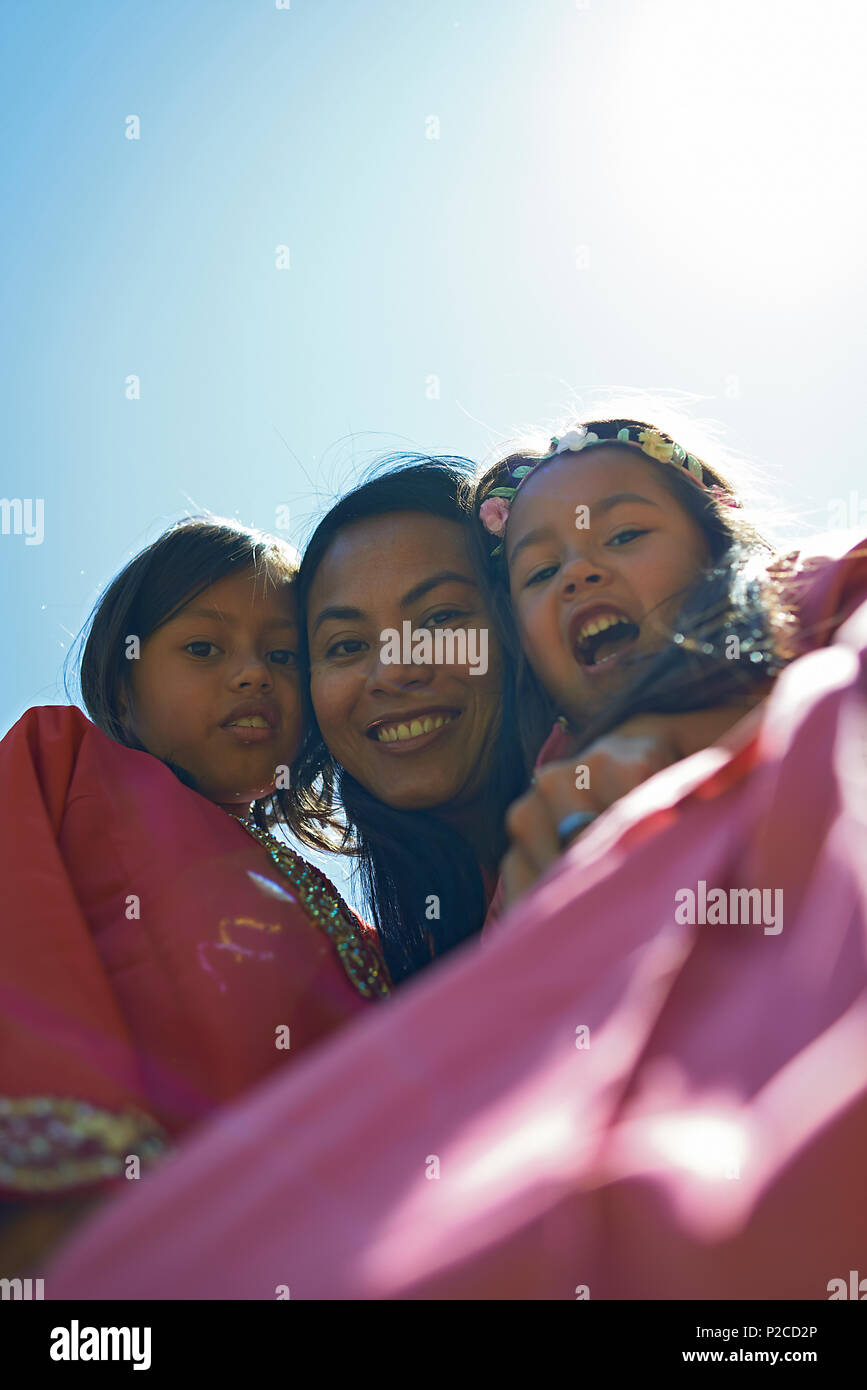 Malay mother and her two young daughters wearing traditional Baju Kurung dresses smiling happily into camera during Hari Raya celebration Stock Photo