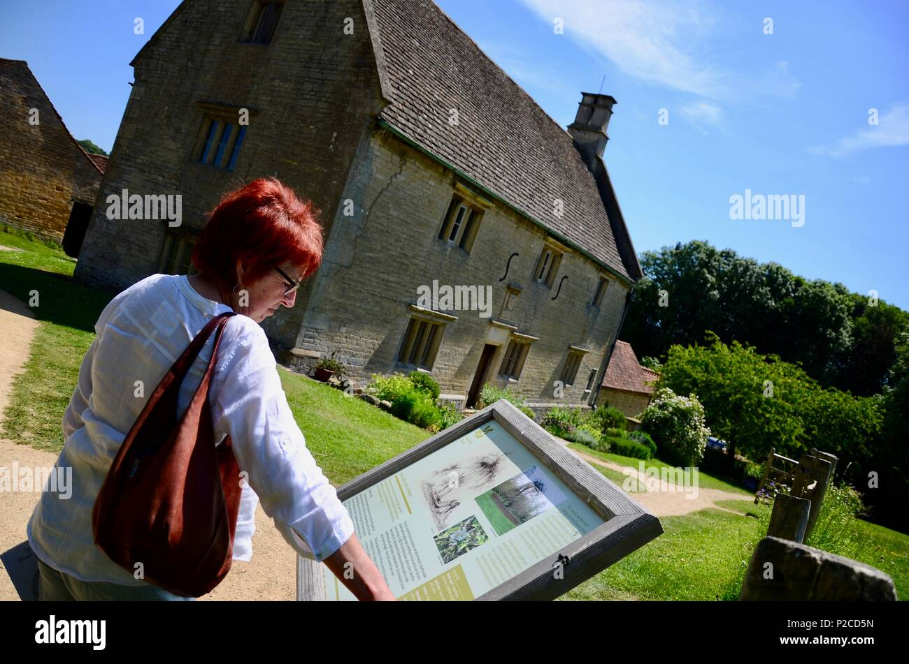 Woman looking at information board, Woolsthorpe Manor, Lincolnshire, home of the scientist and mathematician Sir Isaac Newton. - Stock Image