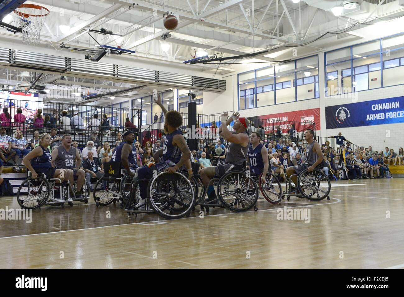 Army Sgt. 1st Class Brant Ireland from Team SOCOM takes a shot against Navy in the wheelchair basketball game during the 2018 Warrior Games held at the Air Force Academy in Colorado Springs June 4, 2018, June 4, 2018. Several members of Team SOCOM advanced to the finals. Created in 2010, the DoD Warrior Games introduce wounded, ill and injured service members and veterans to Paralympic-style sports. Warrior Games showcases the resilient spirit of today's wounded, ill or injured service members from all branches of the military. These athletes have overcome significant physical and behavioral i - Stock Image