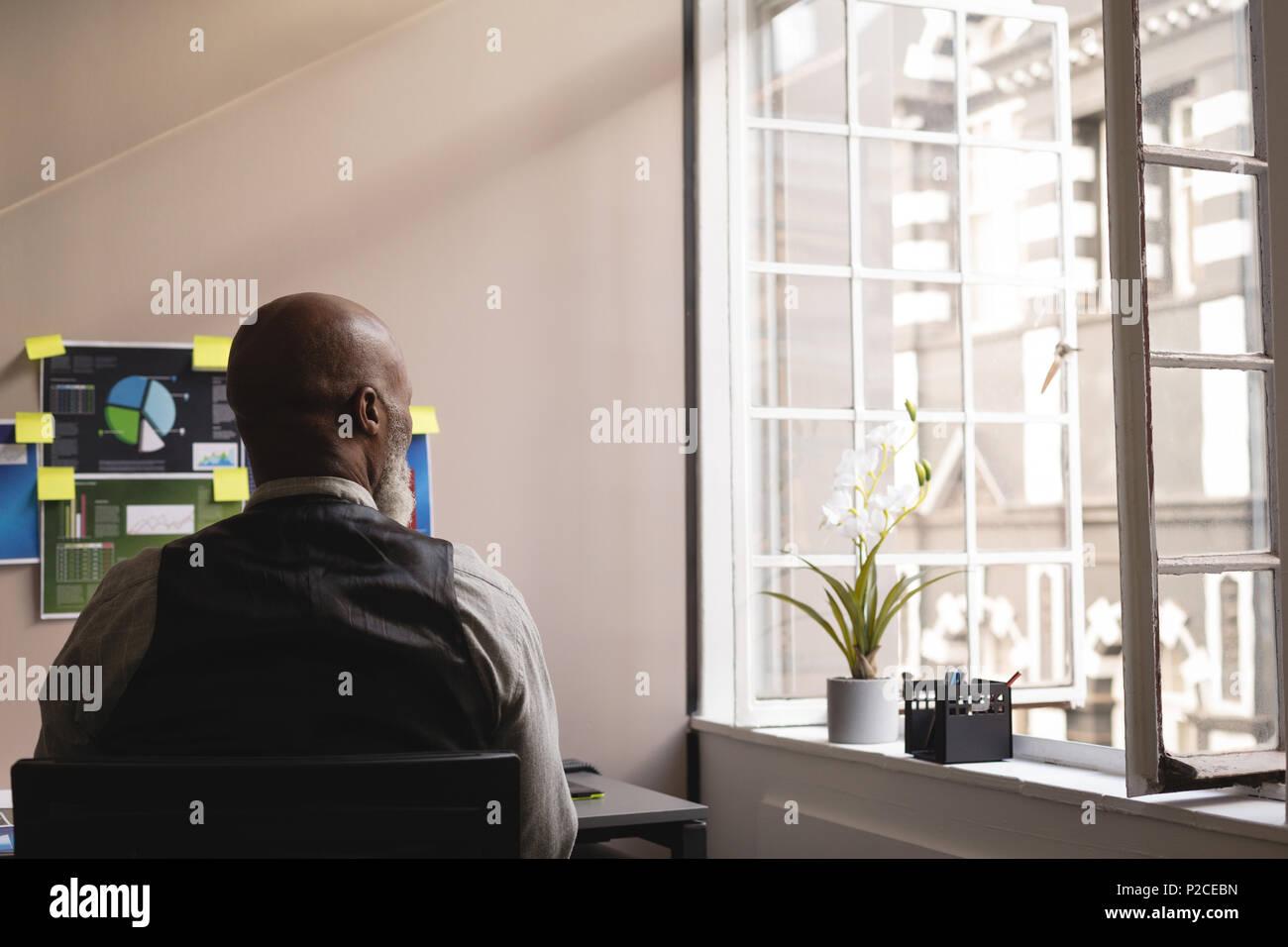 Senior graphic designer relaxing in office - Stock Image