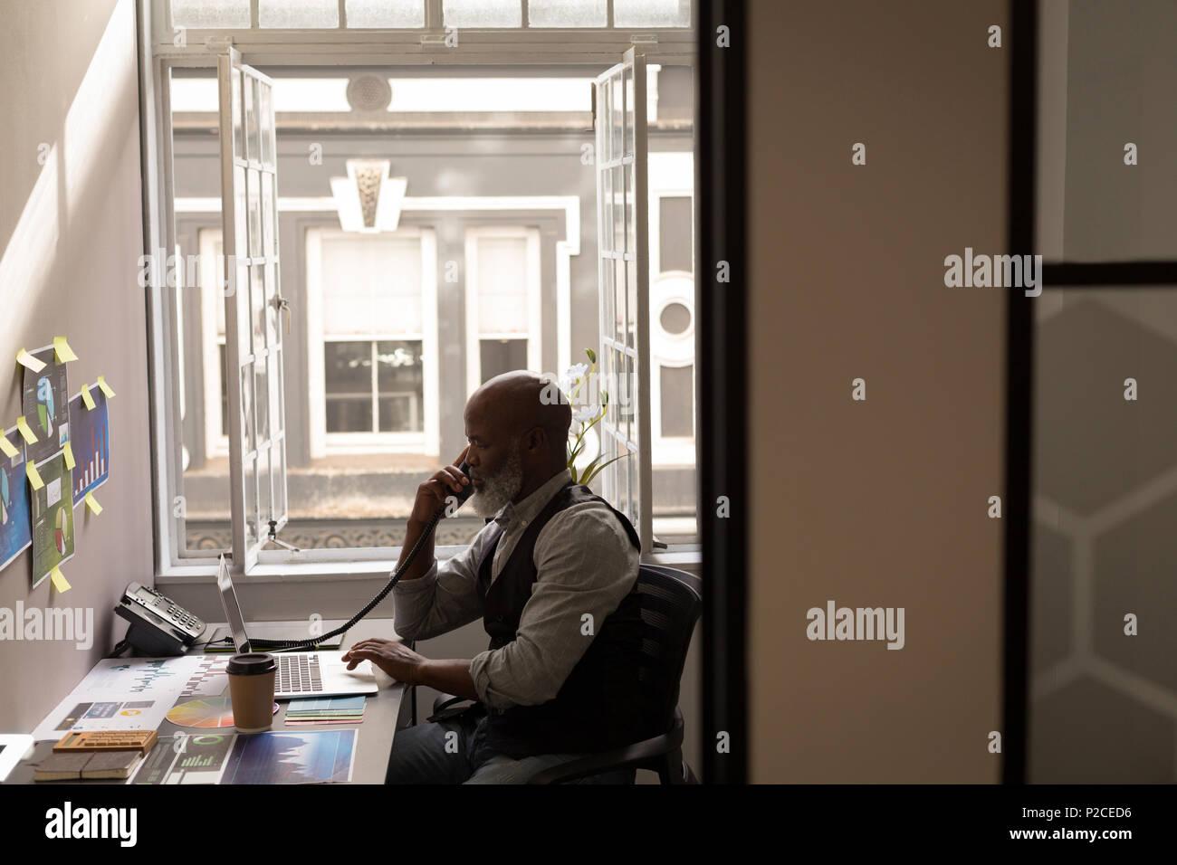 Senior graphic designer talking on landline at desk - Stock Image
